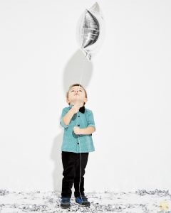 ładnie ubrany chłopiec z balonikiem